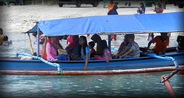 Menggunakan perahu kecil menuju pasir timbul