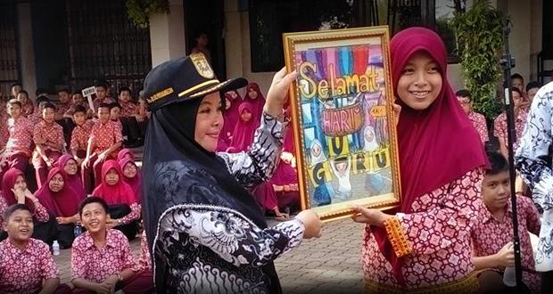 Kepala sekolah SMP Al Kautsar ibu Sri Purwaningsih menerima lukisan bertuliskan selamat hari guru dari Safira Chika Noraliza.