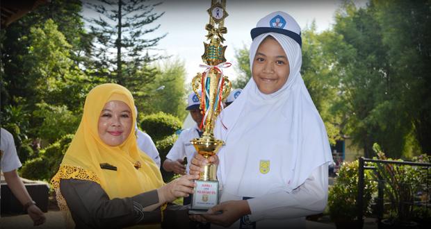 Kepala SMP Al Kautsar Sri Purwaningsih memberikan piala kepada Audreyna Raihan yang berhasil meraih Juara I Olimpiade Matapelajaran IPS para ajang Pra OSN tingkat Kota Bandar Lampung.
