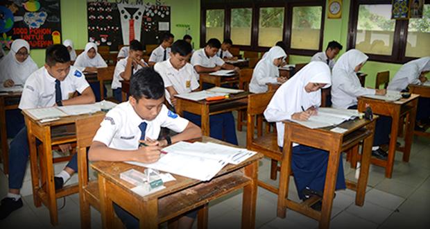 Murid SMP Al Kautsar mengerjakan Ujian Nasional Matematika dengan serius