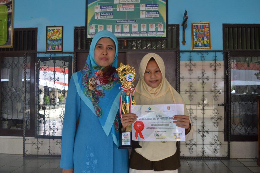 Dalila Nuratifa Syam dan Meri Oktarina berfoto sambil memegang Piala dan Piagam  setelah memenangkan lomba menulis surat untuk presiden