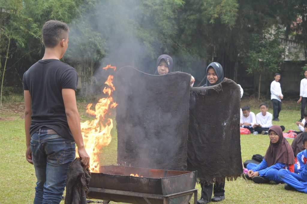 Peserta diklat mempraktekkan cara memadamkan api menggunakan karung basah